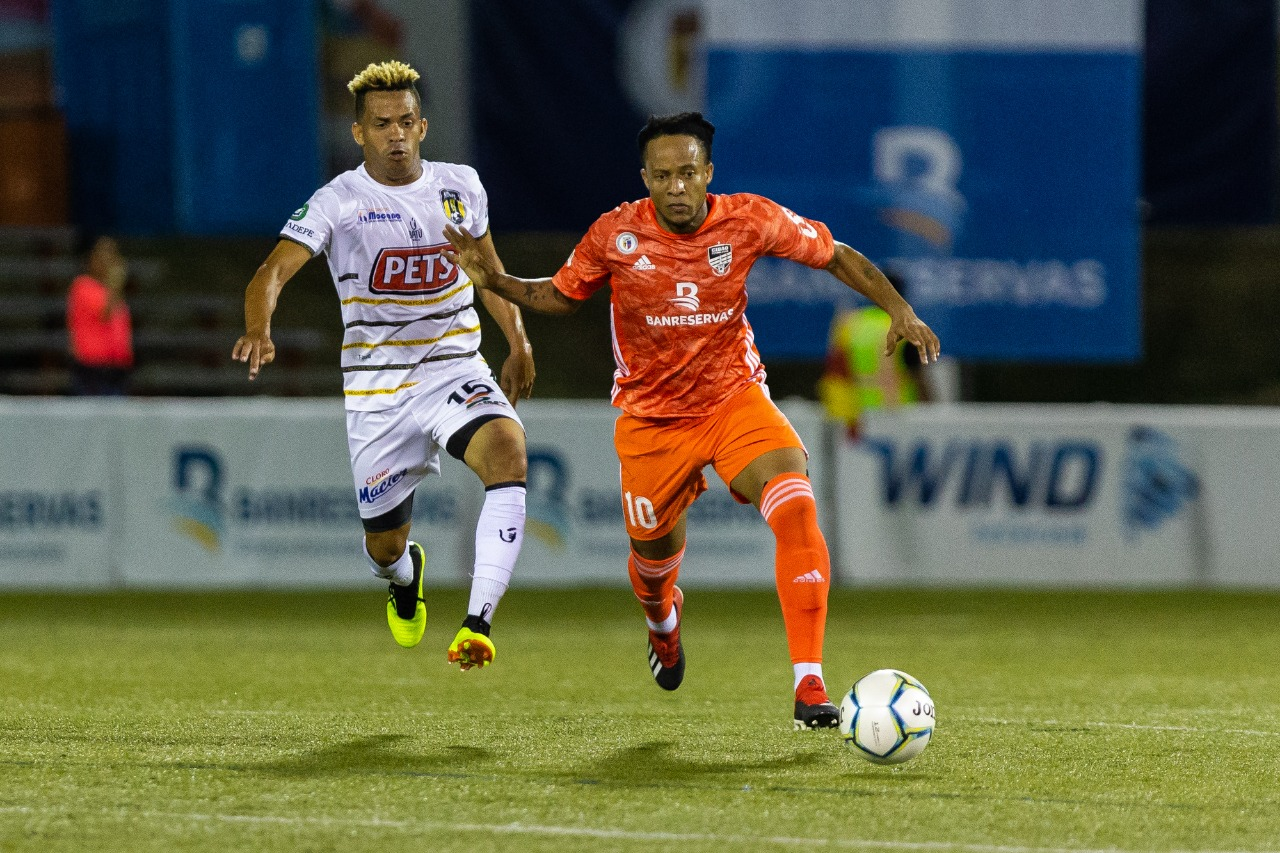 Charles Herold Junior de Cibao FC conduce el balon, marcado por un jugador de Moca FC