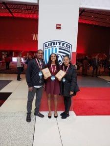 Mia Asenjo y sus padres posan junto a sus premios All American